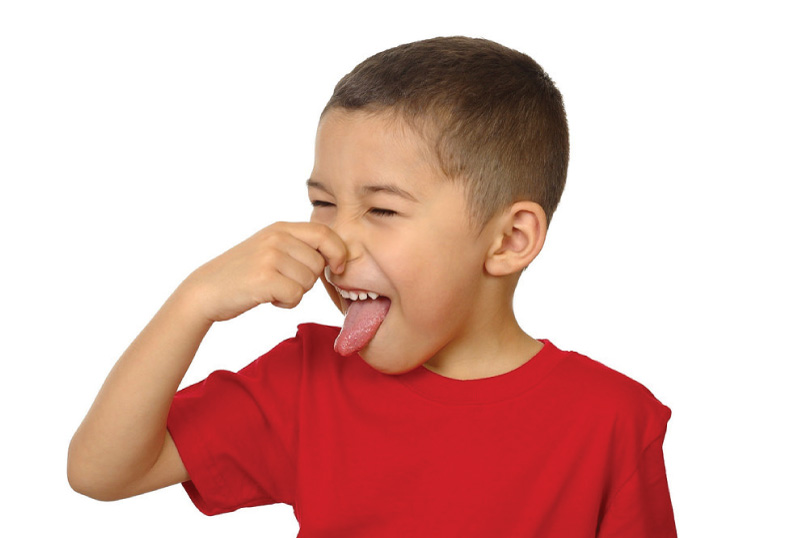 Young boy holding nose for bad smell